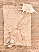 Brown crumpled paper with seashells on wooden texture — Stock Photo