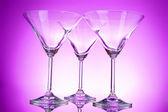 Three empty martini glasses on purple background — Stock Photo
