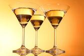 Three martini glasses on yellow background — Stock Photo