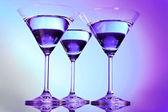 Three martini glasses on purple background — Stock Photo