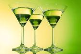 Three martini glasses on green background — Stock Photo