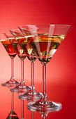 Four martini glasses on red background — Stock Photo