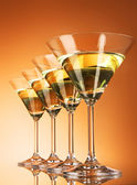 Four martini glasses on yellow background — Stock Photo