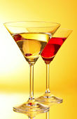 Brýle s alkoholický nápoj na žluto hnědé pozadí — Stock fotografie