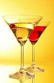 Glazen met alcoholische drank op geel-bruine achtergrond — Stockfoto