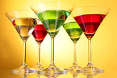 A few glasses of alcoholic drinks in a yellow-brown background — Stock Photo