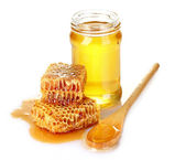 Beautiful combs, spoon and honey in jar isolated on white — Stock Photo