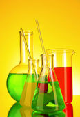 Laboratory glassware on yellow background — Stock Photo