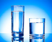 Dos vasos de agua sobre fondo azul — Foto de Stock