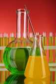 Flask on test-tubes background — Stock Photo