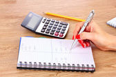 Hand, notepad and calculator — Stockfoto