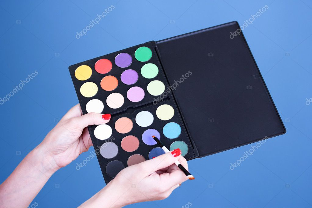 Eye shadows in hand on blue background — Stock Photo #6791161