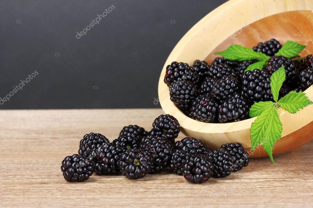 Beautiful blackberries in wooden bowl on gray background — Foto Stock #6792483