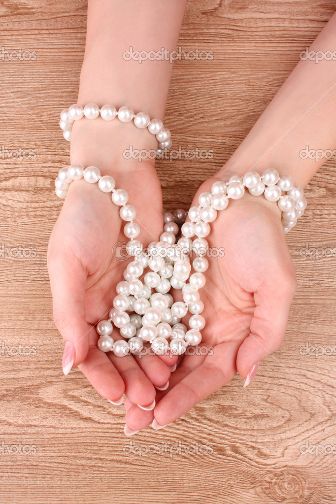 Woman hand with pearls on wooden background — Stock Photo #6796485