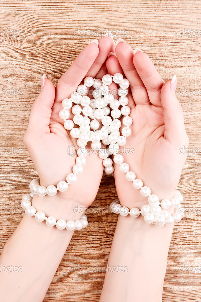 Woman hand with pearls on wooden background  Stock Photo #6796490