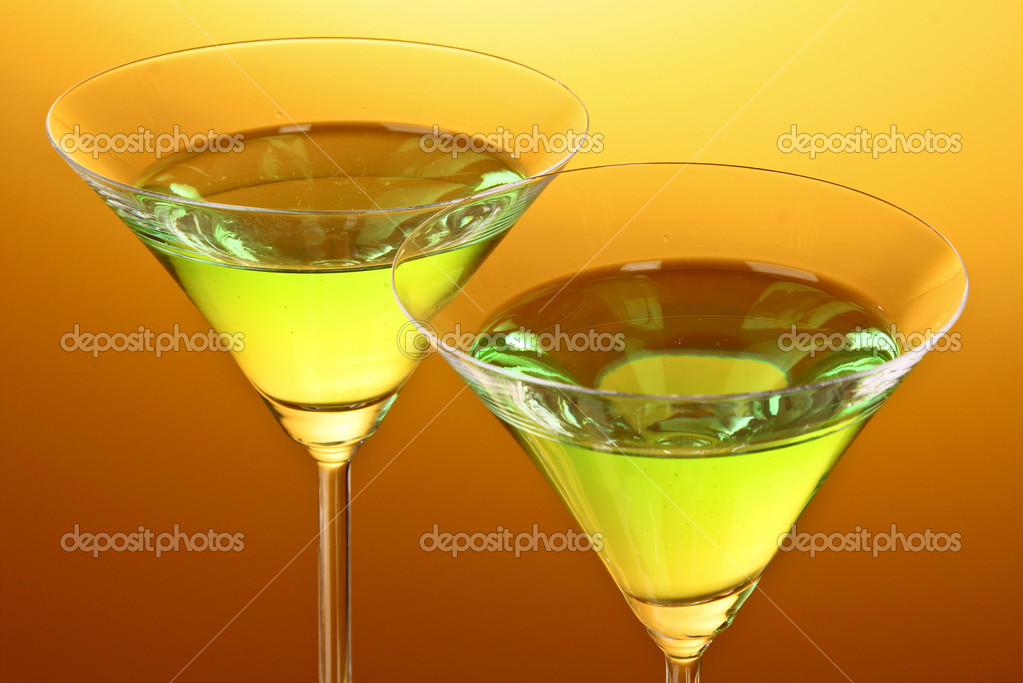 Glass with a green alcoholic beverage to a yellow-brown background — Stock Photo #6798802