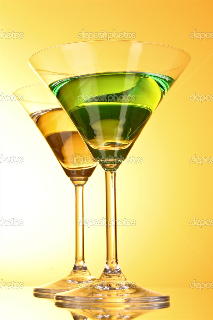 Glass with a green alcoholic beverage to a yellow-brown background — Stock Photo #6798839