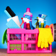 Cleaning supplies in basket on blue background — Stock Photo