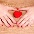 Red heart in hands on wooden background — Stock Photo