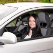 Young brunette woman in new car — Stock Photo