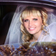Beautiful bride in limousine - Stock Photo