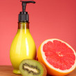 Fruity body lotion, grapefruit and kiwi fruit on red backgroun — Stock Photo #6805905