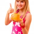 Young girl thumbs up with tea cup isolated on white — Stock Photo #6805930