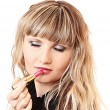 Beautiful young girl making up her lips with lipstick — Stock Photo