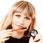 Beautiful young woman applying makeup with brush — Stock Photo