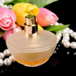 Brown bottle of parfume, tulips and pearls on black — Stock Photo #6806182