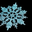 Blue shiny snowflake isolated on black — Photo