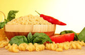 Spaghetti with onion, spices and basil on a yellow background — Stock Photo