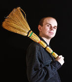 Janitor man with besom on black background — Stock Photo
