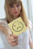 Sad girl with sad smile on note pad — Stock Photo