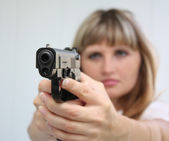 Girl aiming with gun — Stock Photo