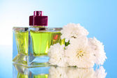 Perfume bottle on blue background — Stock Photo