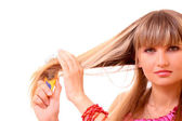 Young woman doing her long blond hair isolated on white — Stock Photo