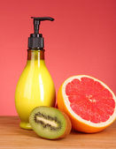 Fruity body lotion, grapefruit and kiwi fruit on a red backgroun — Stock Photo