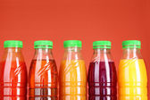 Bottles of juice with ripe fruits on red background — Foto Stock