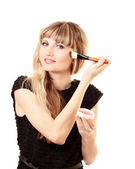 Beautiful young woman applying makeup with brush isolated on wh — Stock Photo