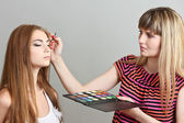 Make-up artist applying eye shadows on beautiful model — Stock Photo