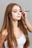 Aplicación de sombra de ojos en una muchacha hermosa — Foto de Stock