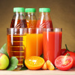 Different juices and fruits on wooden table on brown background — Stock Photo