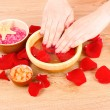Hands in water with rose petals — Stock Photo
