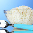Tasty cottage cheese in bowl and spoon — Stock Photo