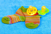 Bright baby socks and baby soothers — Stock Photo