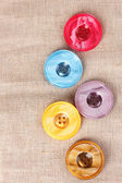 Bright sewing buttons on gray fabric — Stockfoto