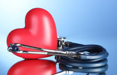 Medical stethoscope and heart on blue background — Stock Photo