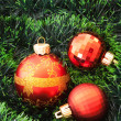 Red Christmas balls and presents  among green new year tree — Stock Photo