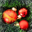 Red Christmas balls and presents among green new year tree — Stock Photo #7288125